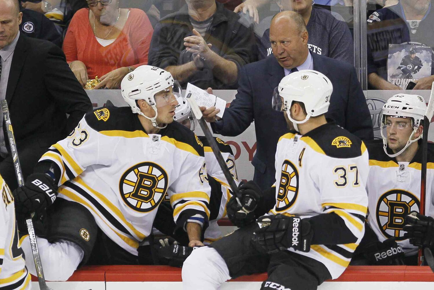 Boston Bruins head coach Claude Julien talks with Brad Marchand (63) and Patrice Bergeron (37) during a commercial break.