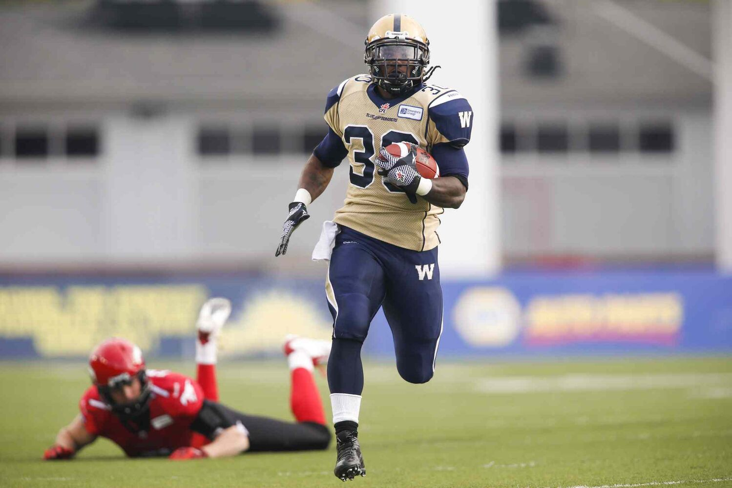 Winnipeg Blue Bombers' Will Ford returns a kick as Calgary Stampeders' Eric Fraser watches him get away during the first half.