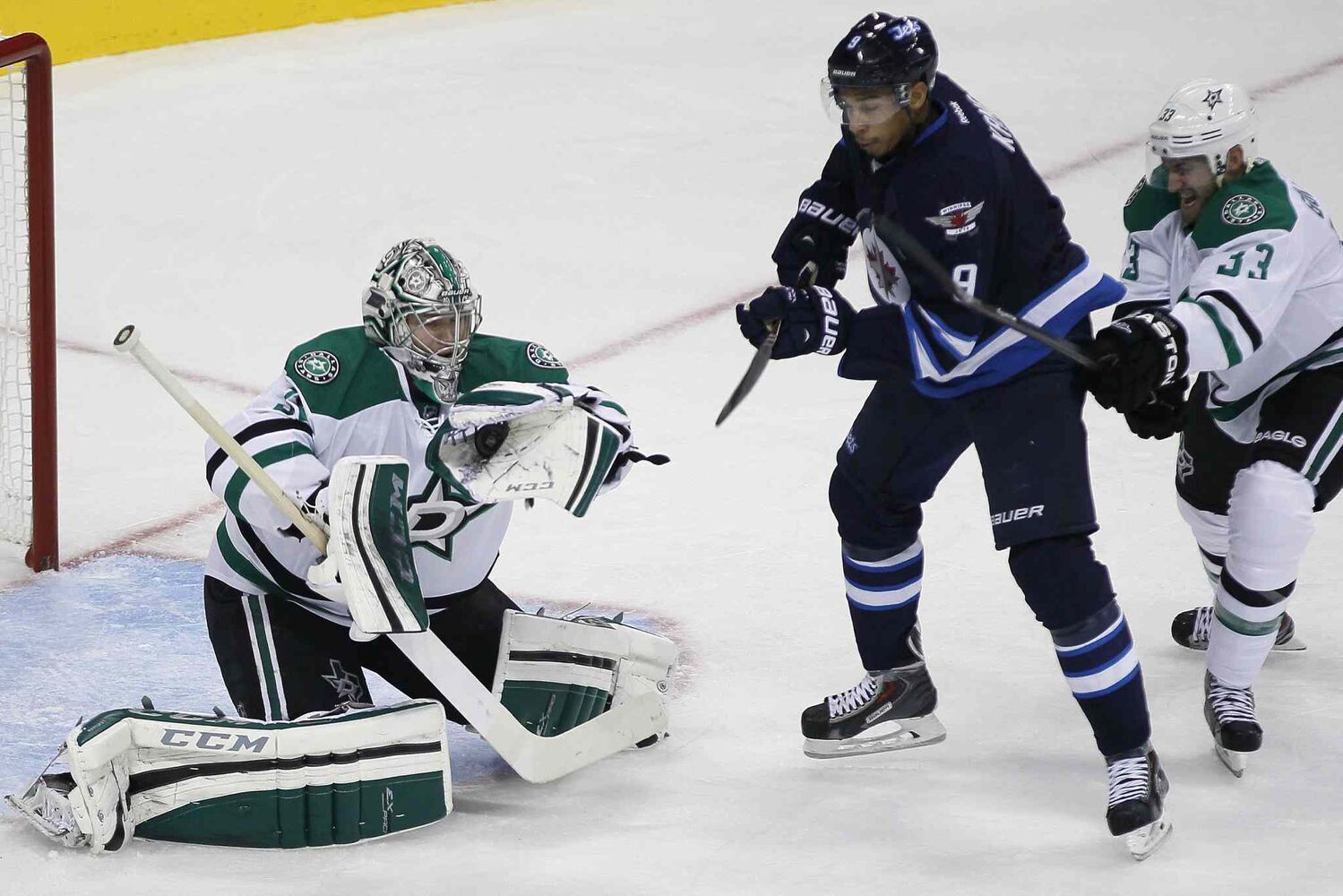 Dallas Stars goaltender Kari Lehtonen (32) grabs the puck as Evander Kane (9) tries to deflect it past him during the first period. (JOHN WOODS / THE CANADIAN PRESS)