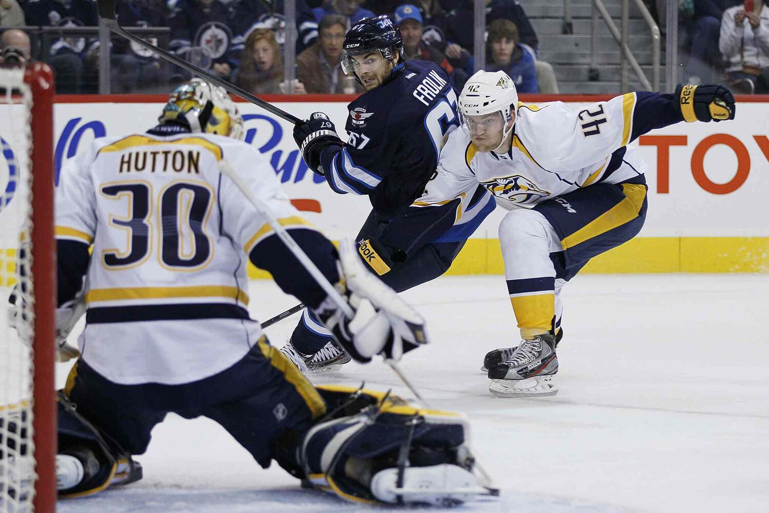 Michael Frolik (67) of the Winnipeg Jets and Nashville Predators' Mattias Ekholm (42) watch as Frolik's shot is saved by Predators goaltender Carter Hutton (30) during the second period.