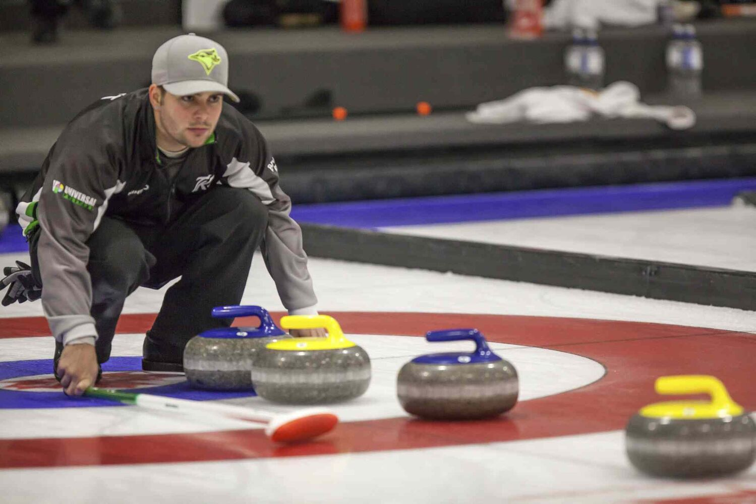 Travis Fanset, of Team Kean examines rocks lined up in front of the button. (Greg Gallinger / Winnipeg Free Press)