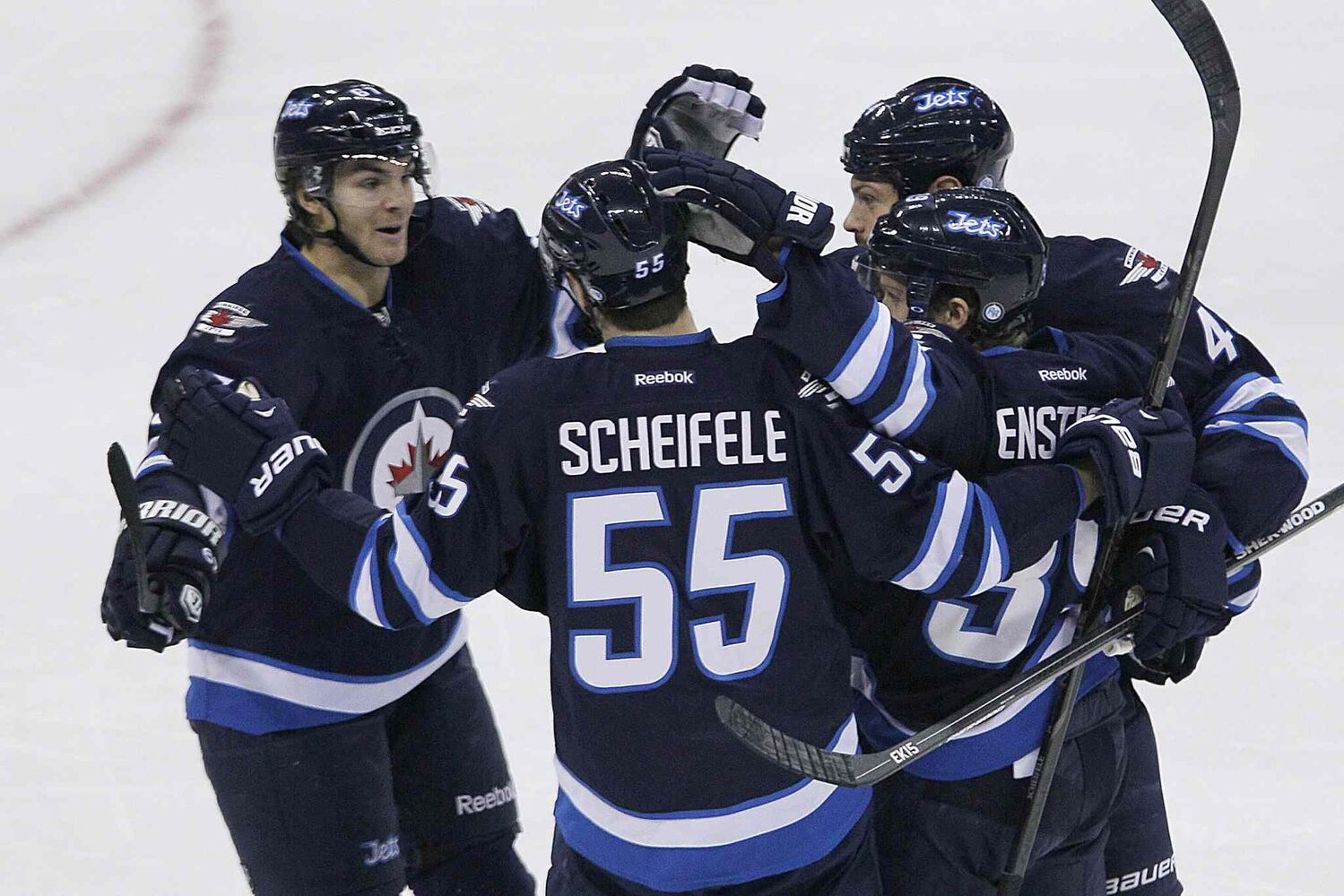 Members of the Winnipeg Jets celebrate a first-period goal by Toby Enstrom (bottom right). The goal would be the Jets' lone marker Saturday afternoon.