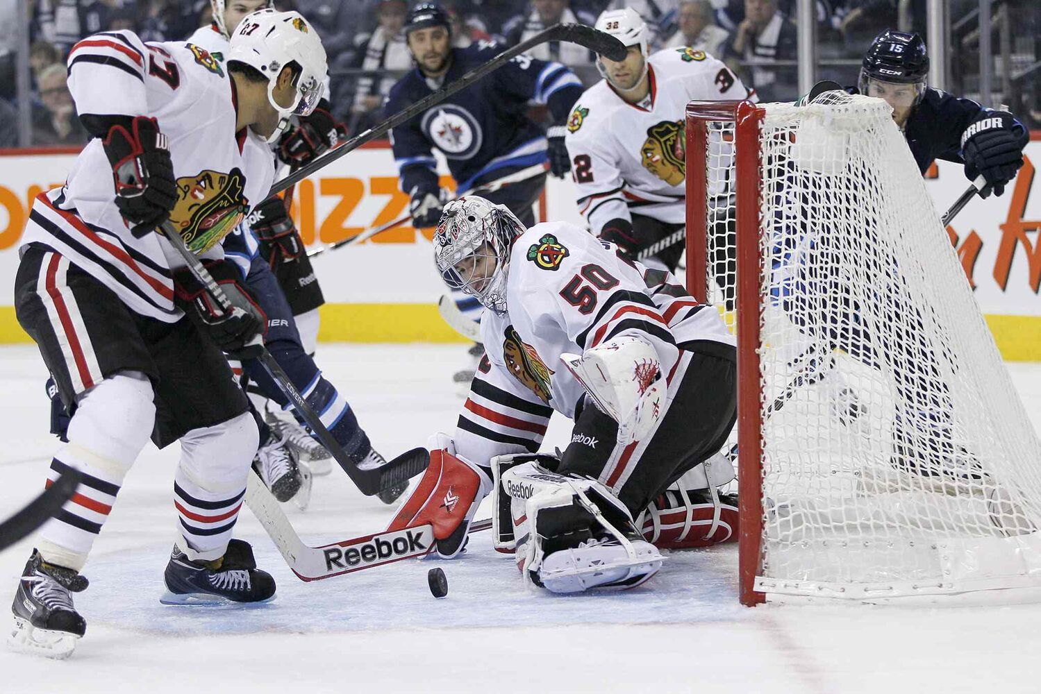 Chicago Blackhawks goaltender Corey Crawford (50) makes a save off a Matt Halishchuk shot as Johnny Oduya (left) picks up the rebound during the second period.