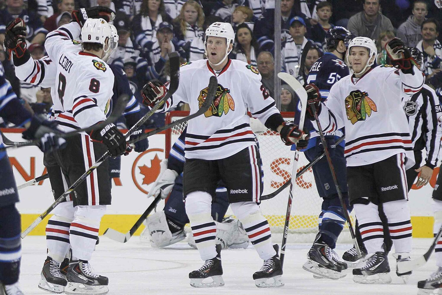 Chicago Blackhawks' Bryan Bickell (centre) and Andrew Shaw (right) celebrate Nick Leddy's goal against the Winnipeg Jets during the second period.