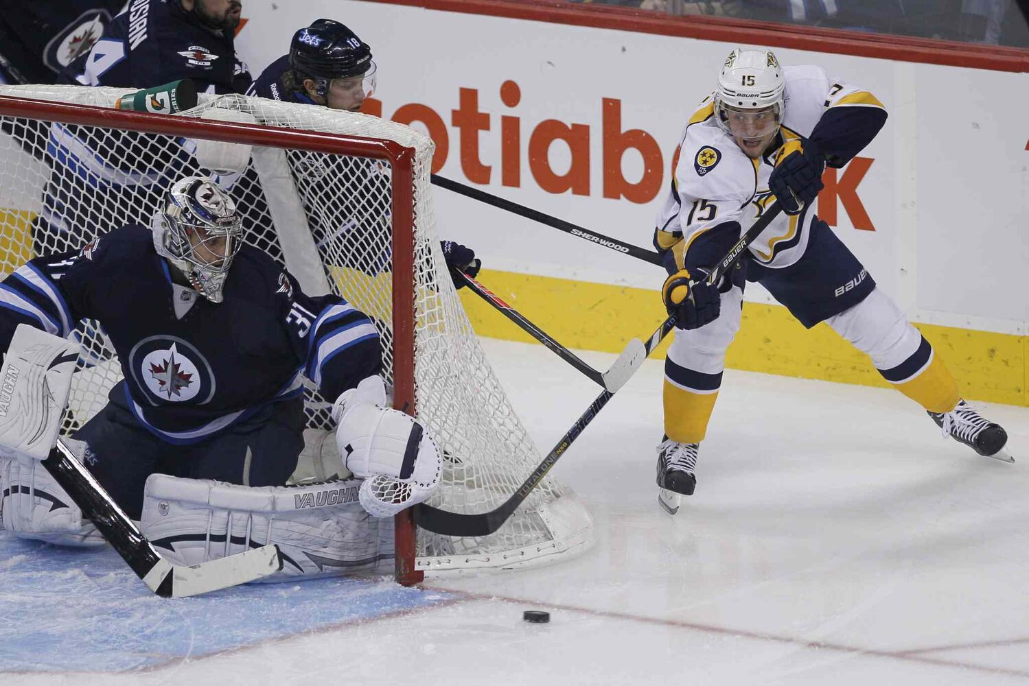 Nashville Predators' Craig Smith (15) makes a pass out in front of Winnipeg Jets' goaltender Ondrej Pavelec during the first period.
