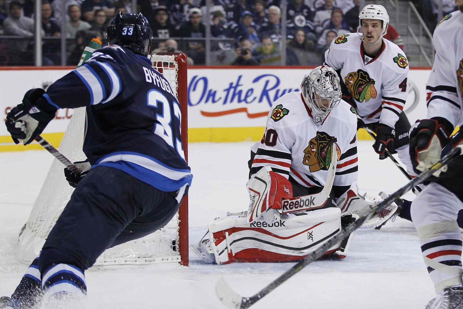 Winnipeg Jets defenceman Dustin Byfuglien gets a shot past Chicago Blackhawks goaltender Corey Crawford (50) for a goal during the second period.