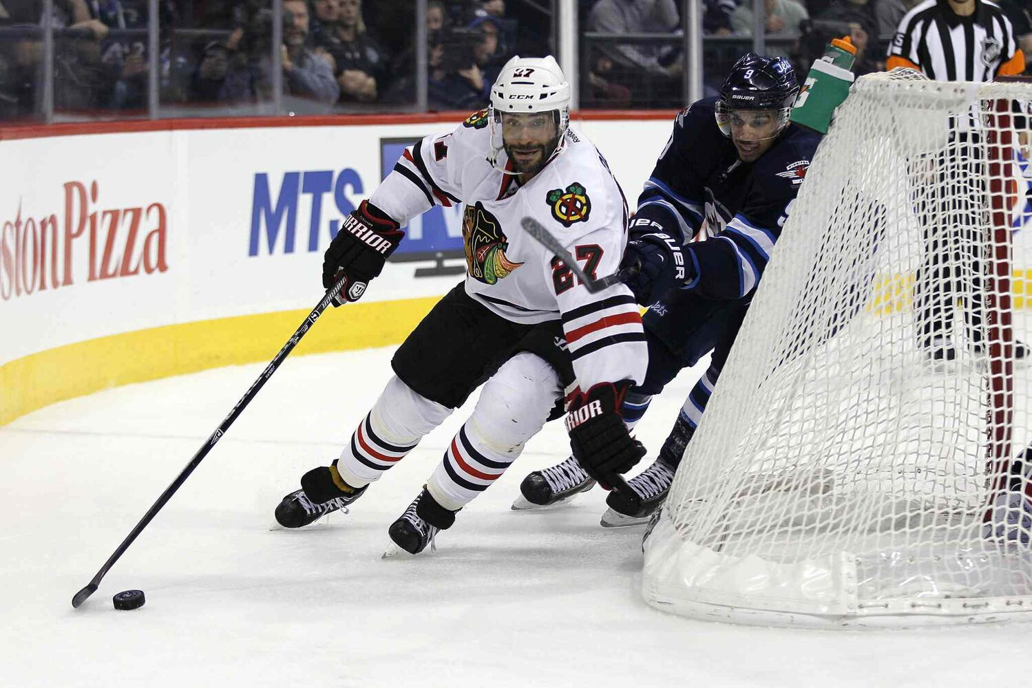 Winnipeg Jets forward Evander Kane (9) chases Chicago Blackhawks defenceman Johnny Oduya (27) behind his net during the second period.