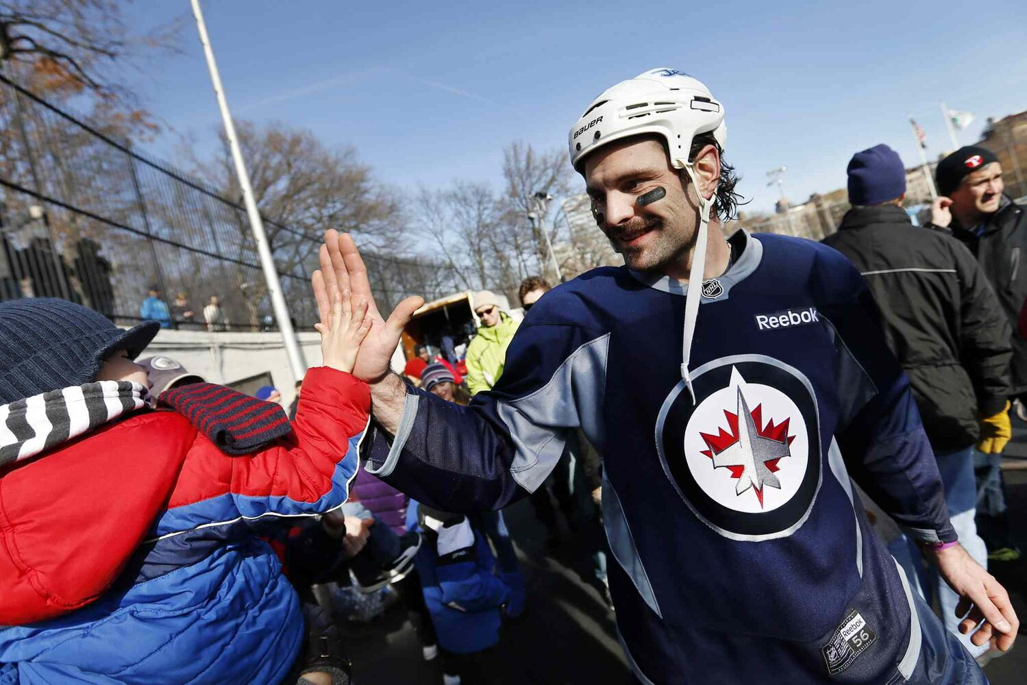 Winnipeg Jets defenceman Mark Stuart high-fives four-year-old fan James MacDonald after practice. (Jason DeCrow / The Associated Press)