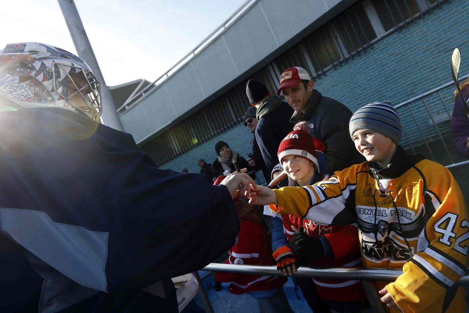 Al Montoya (left) signs autographs for 10-year-old fans Alexander Giebler (centre) and Keith McGann. (Jason DeCrow / The Associated Press)