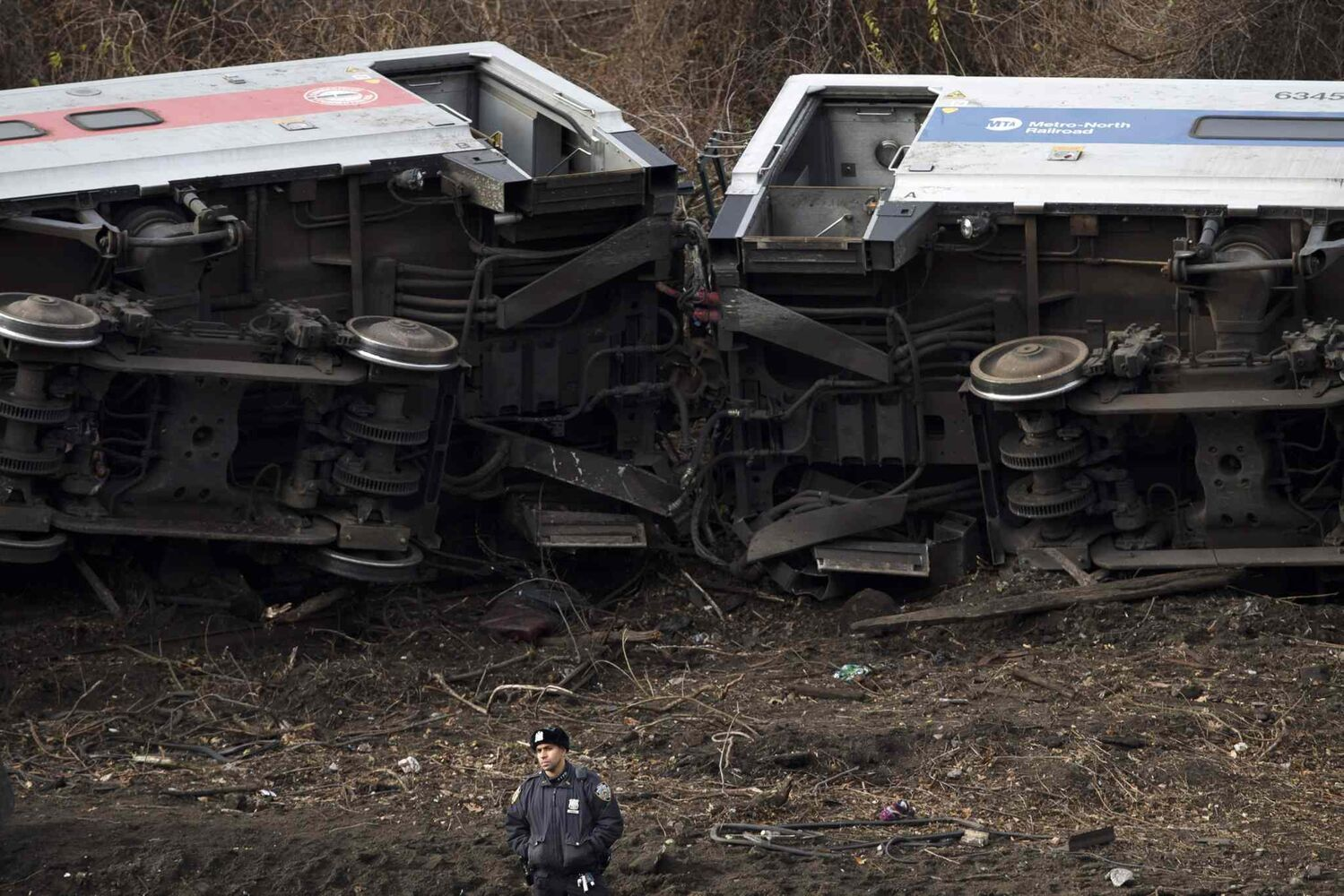 A police officer stands guard at the scene of a Metro-North passenger train derailment in the Bronx borough of New York Sunday. (John Minchillo / The Associated Press)