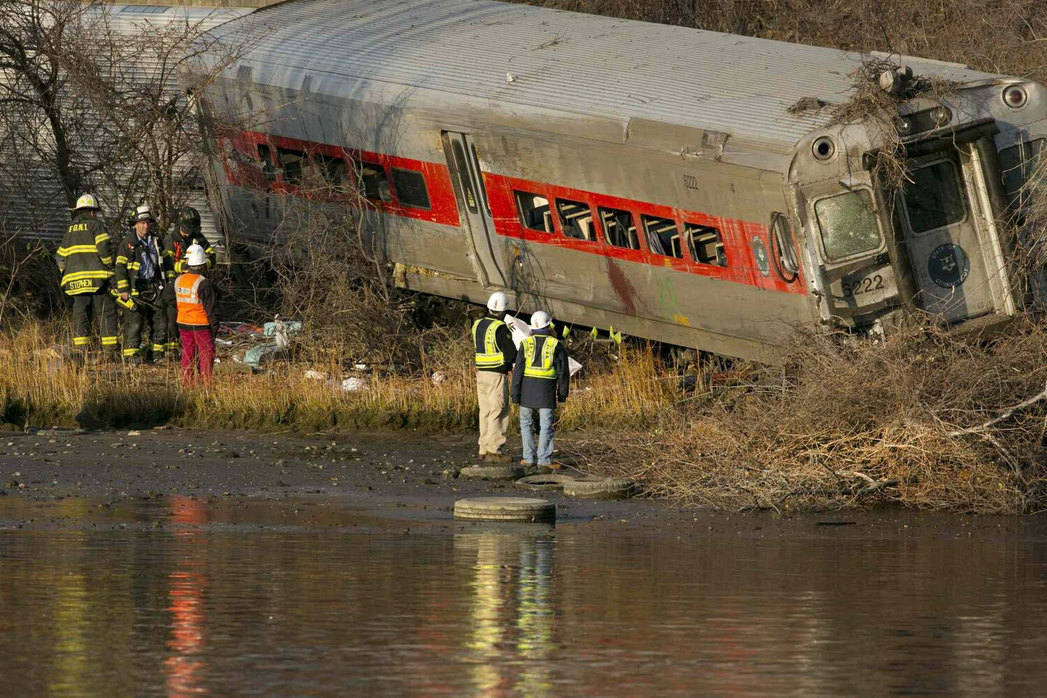 Officials with the National Transportation Safety Board inspect a derailed Metro North commuter train.