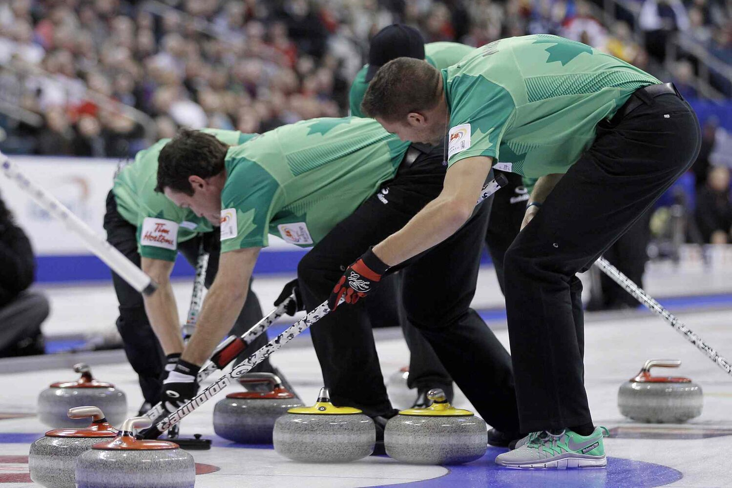 Tyrel Griffith (left), Rick Sawatsky and John Morris (right) sweep one of John Cotter's stones to score two points in the fifth end. (John Woods / The Canadian Press)