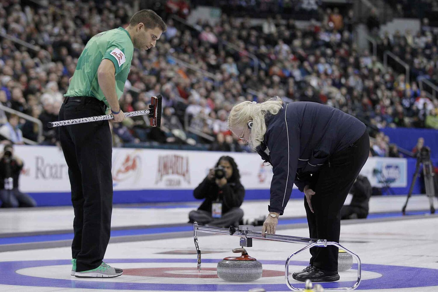 Skip John Morris watches as an official measures stones in the fifth end. (John Woods / The Canadian Press)