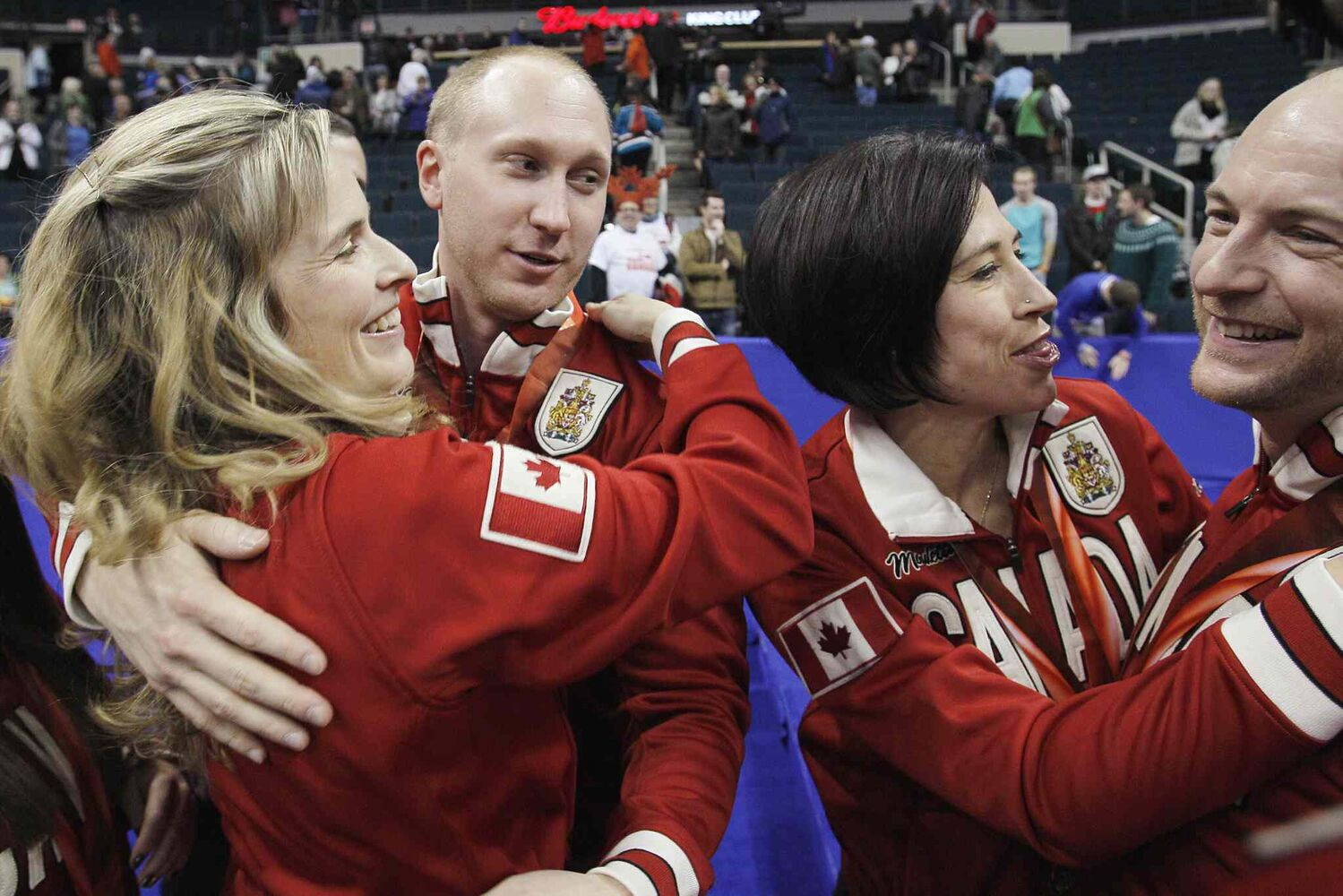 Brad Jacobs (centre left) and Ryan Fry (right) are congratulated by women's winners Jennifer Jones (left) and Jill Officer. (John Woods / The Canadian Press)