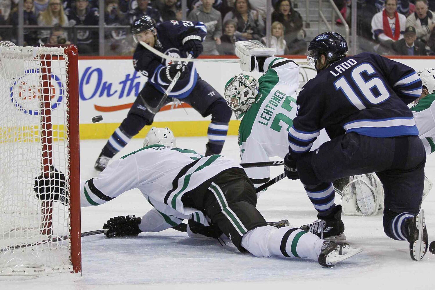 Blake Wheeler (top) puts the puck past Jamie Oleksiak (bottom) and goaltender Kari Lehtonen (centre right) as Andrew Ladd looks on during the second period.