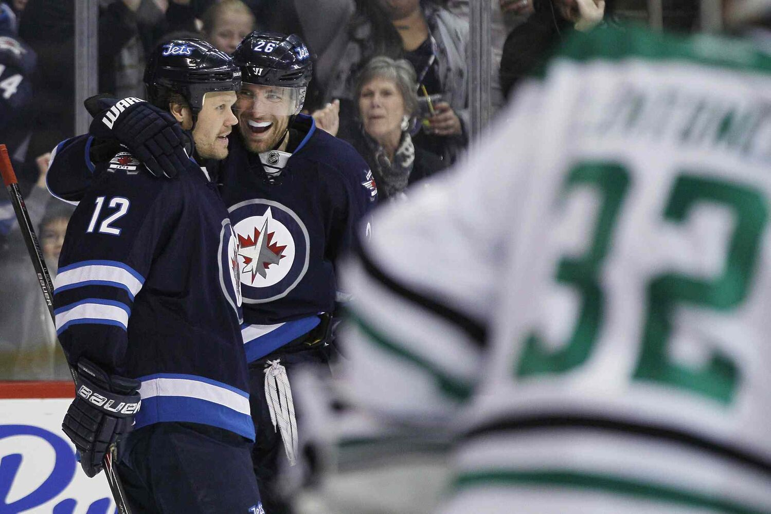 Olli Jokinen (left) and Blake Wheeler (centre) celebrate Wheeler's goal against Dallas Stars goaltender Kari Lehtonen during the second period. (JOHN WOODS / THE CANADIAN PRESS)