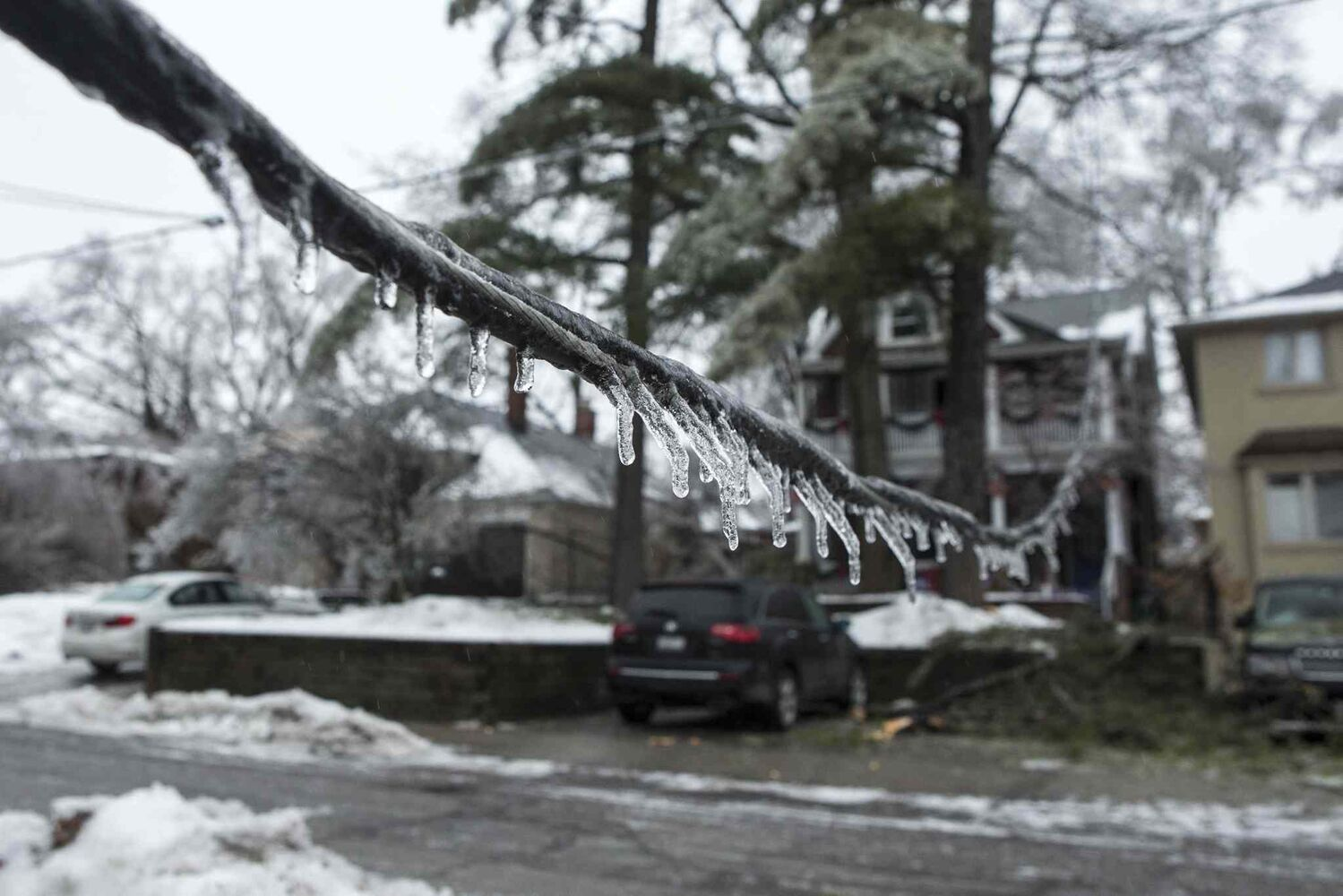 Icicles hang from a downed power line on a residential street in Toronto Sunday. Over 250,000 people face up to 72 hours without electricity after a heavy storm. (Chris Young / The Canadian Press)