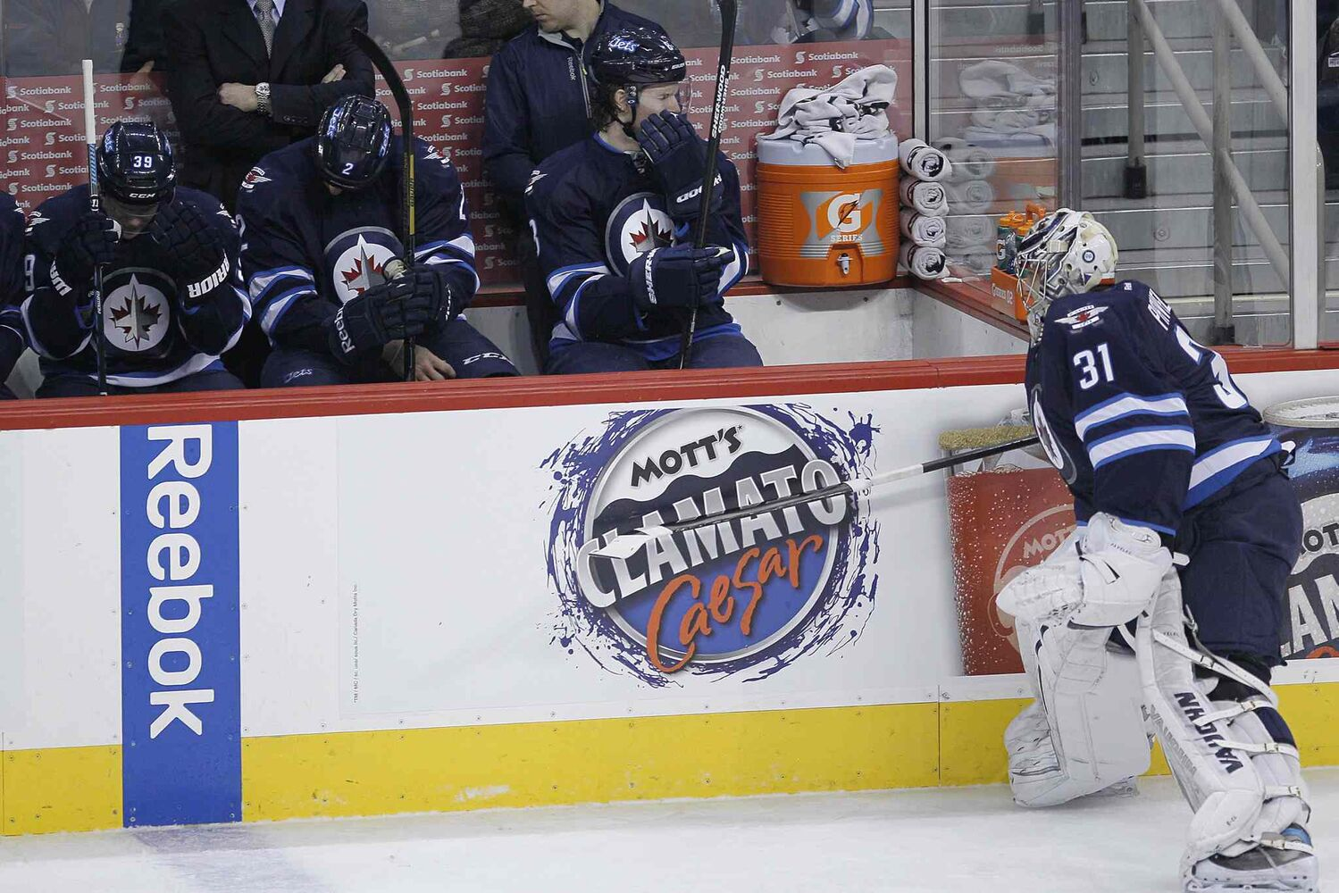 Winnipeg Jets goaltender Ondrej Pavelec (right) slams his stick against the boards in anger after being pulled during the first period.