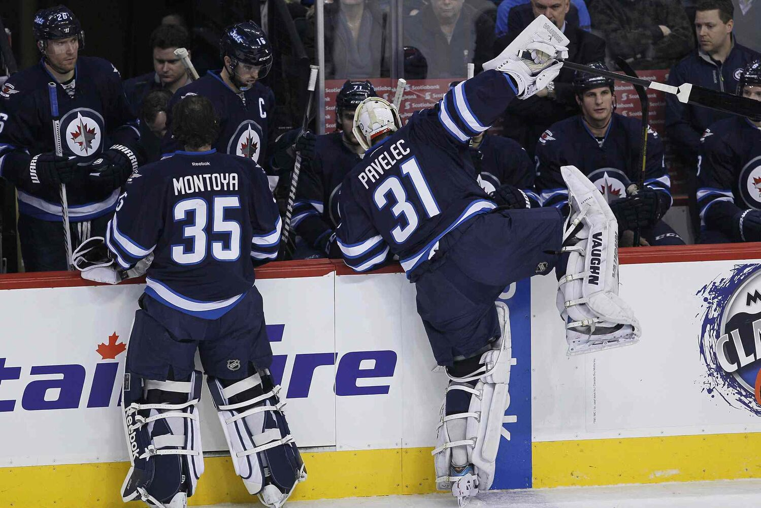 Winnipeg Jets goaltender Ondrej Pavelec (right) climbs over the boards in frustration after being pulled during the first period. Al Montoya (left) came in to replace Pavelec.