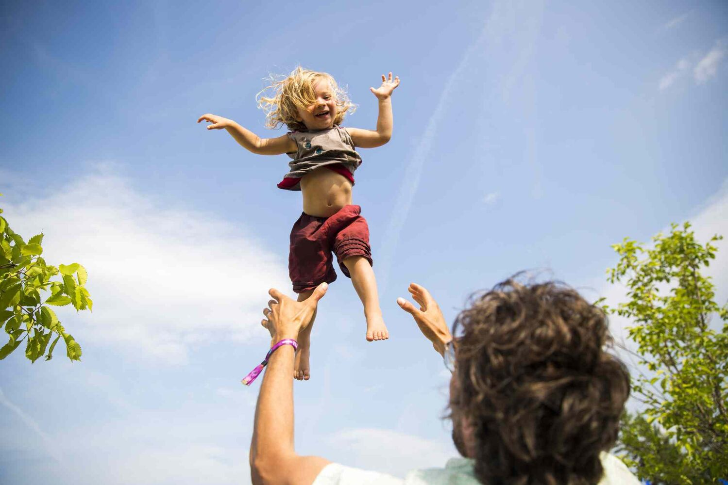 Ari Octavio gets thrown in the air by his dad at the Winnipeg Folk Festival at Birds Hill Provincial Park on Saturday, July 11, 2015.   Mikaela MacKenzie / Winnipeg Free Press (Winnipeg Free Press)