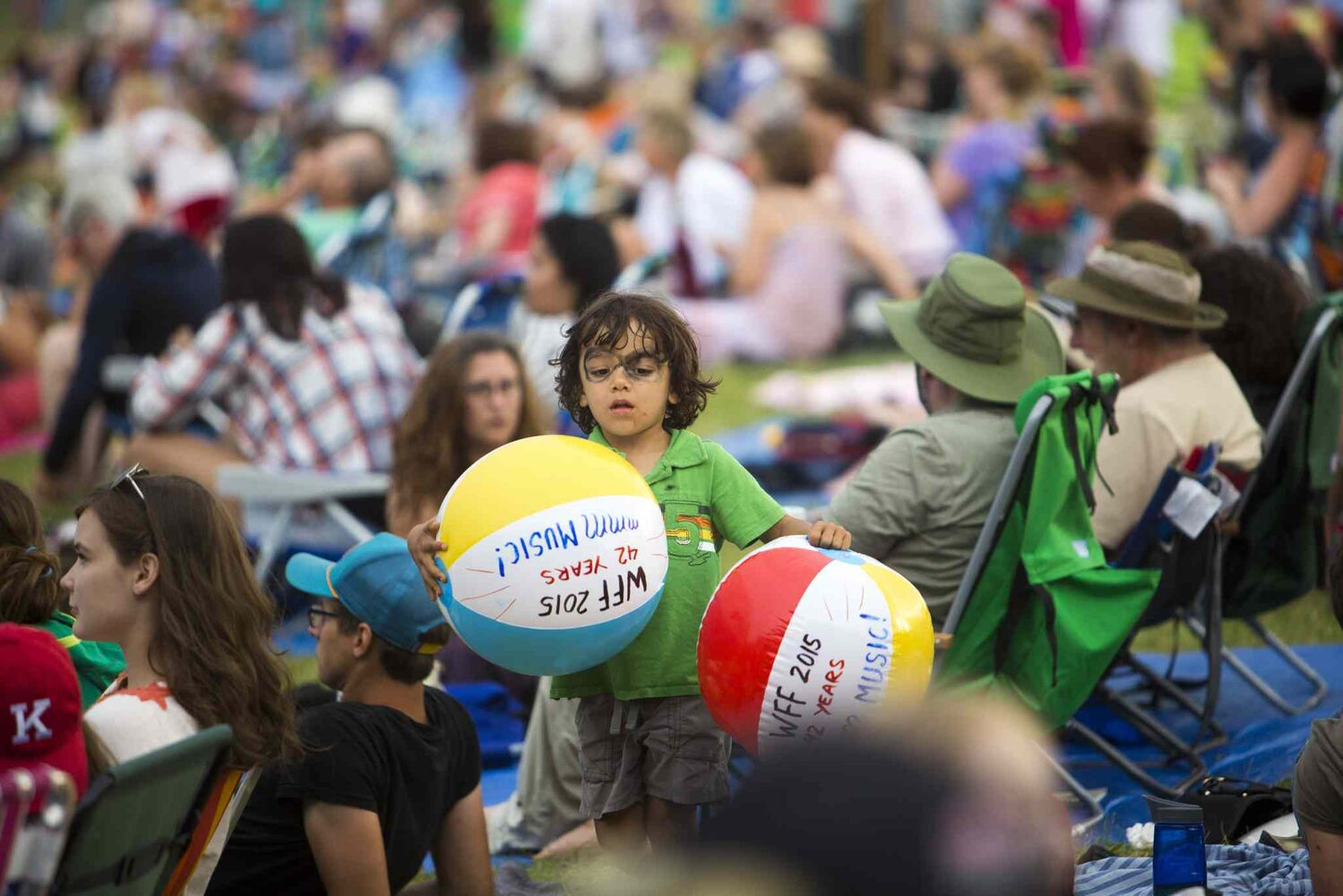 A kid carries beach balls through the crowd at the Winnipeg Folk Festival at Birds Hill Provincial Park on Saturday, July 11, 2015.   Mikaela MacKenzie / Winnipeg Free Press (Winnipeg Free Press)