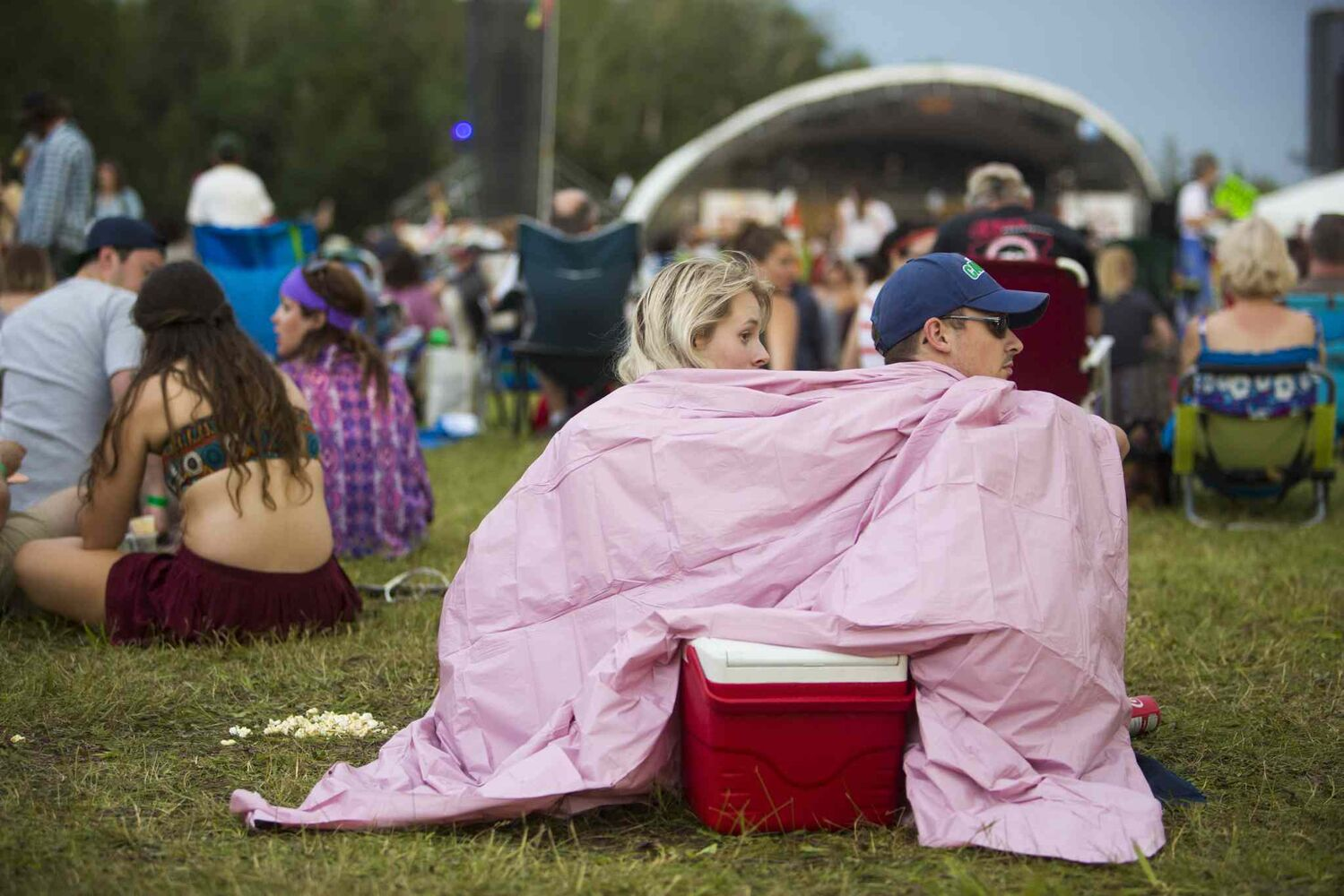Elensia Herda and Jordan DeVisser cuddle under a poncho to keep dry at the Winnipeg Folk Festival at Birds Hill Provincial Park on Saturday, July 11, 2015.   Mikaela MacKenzie / Winnipeg Free Press (Winnipeg Free Press)