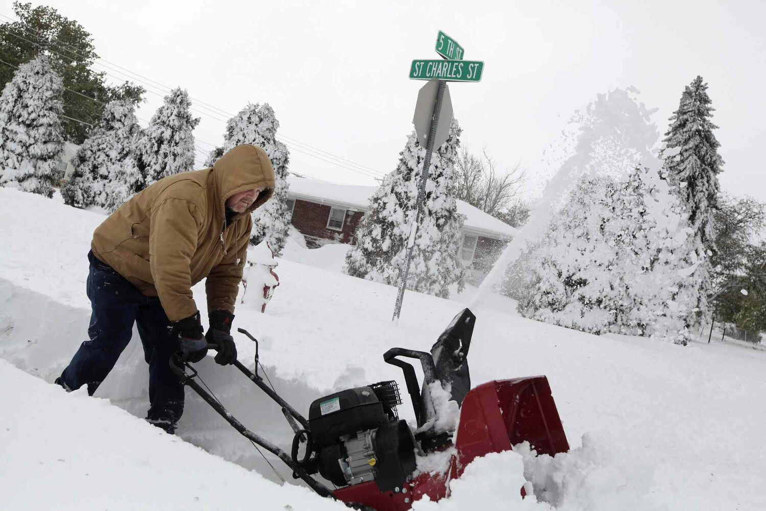 Don Stritecky clears the sidewalk in front of his home with a snow blower in Rapid City, S.D., Saturday, Oct. 5, 2013. South Dakota emergency agencies are asking snowmobile operators in the Rapid City area to help find motorists stranded by an autumn storm.  (Benjamin Brayfield / The ASsociated Press)