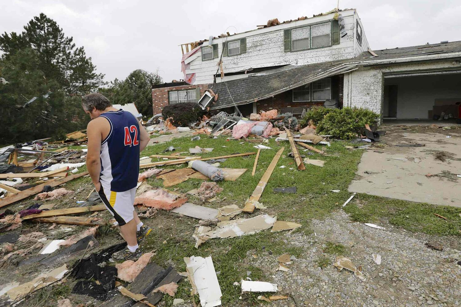 Travis Randall walks through the debris-strewn yard of his parent's home in Hickman, Neb., Friday, Oct. 4, 2013, after it was struck by a tornado. (Nati Harnik / The Associated Press)