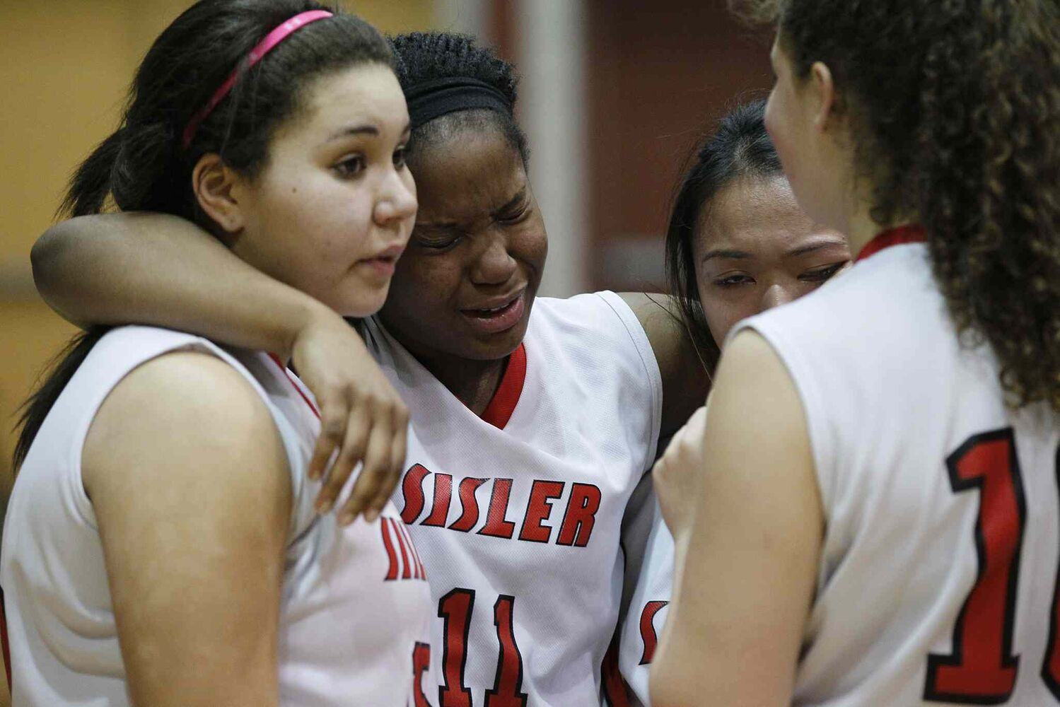 Kyanna Giles (11) cries with teammates after the Sisler Spartans were defeated by the Vincent Massey Trojans in the championship game. It was the Spartans' only loss this season. (JOHN WOODS / WINNIPEG FREE PRESS)