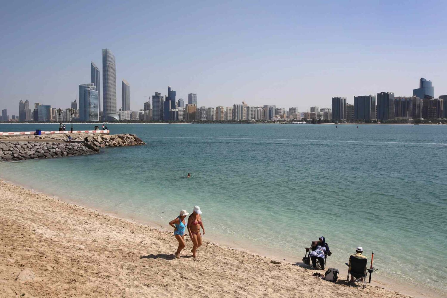 With the city skyline in background, two western tourists in their swimsuits pass local residents as they stroll on the beach in Abu Dhabi, United Arab Emirates.