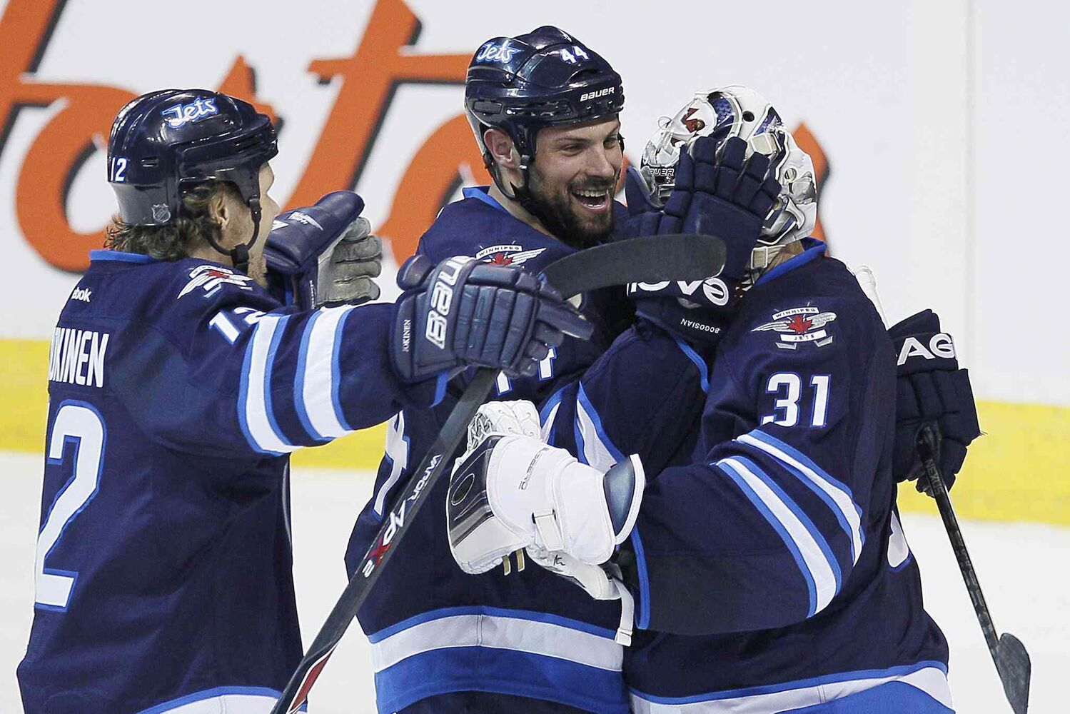 Winnipeg Jets' Olli Jokinen (12), Zach Bogosian (44), and goaltender Ondrej Pavelec (31) celebrate a win over the Phoenix Coyotes in a shoot-out during NHL action in Winnipeg on Thursday. The Jets won 3-2.