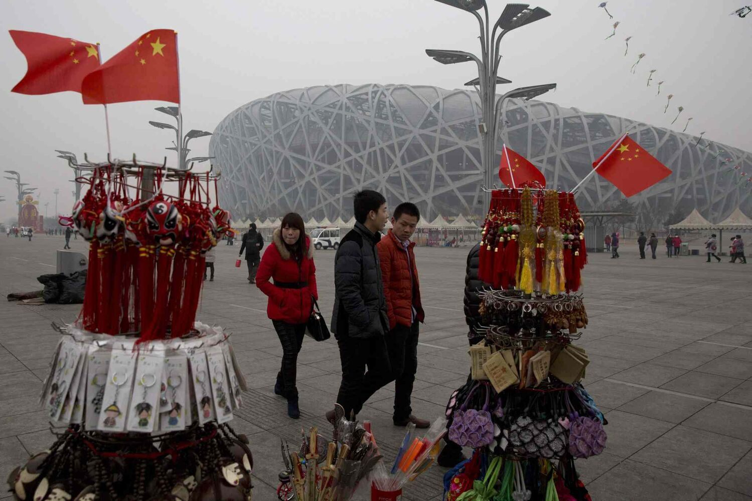 Tourists pass by memorabilia on sale near the iconic Bird's Nest National Stadium in Beijing, China. Few tourists are willing to pay more than $8 to tour the facility as enthusiasm for the 2008 Games fades, and the venue has struggled to fill its space with events. (Ng Han Guan / The Associated Press)