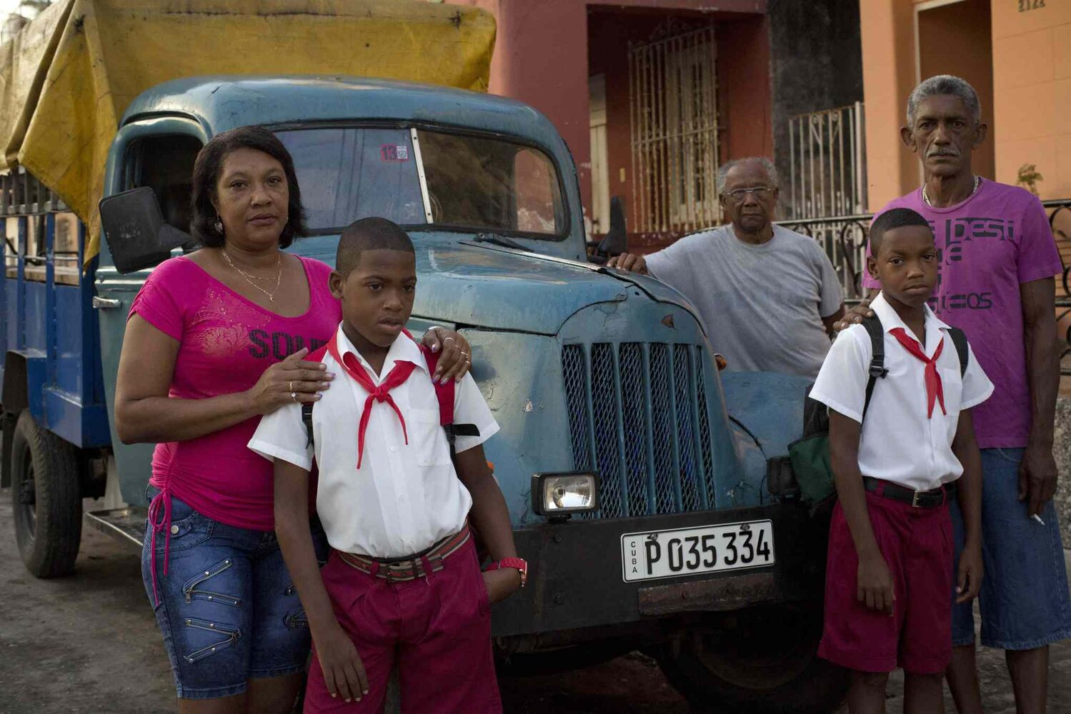 Eleven-year-old twin brothers Arian and Adrian Cueto pose for portraits in their school uniforms alongside their parents and grandfather as they gather around their family's truck in Havana, Cuba.