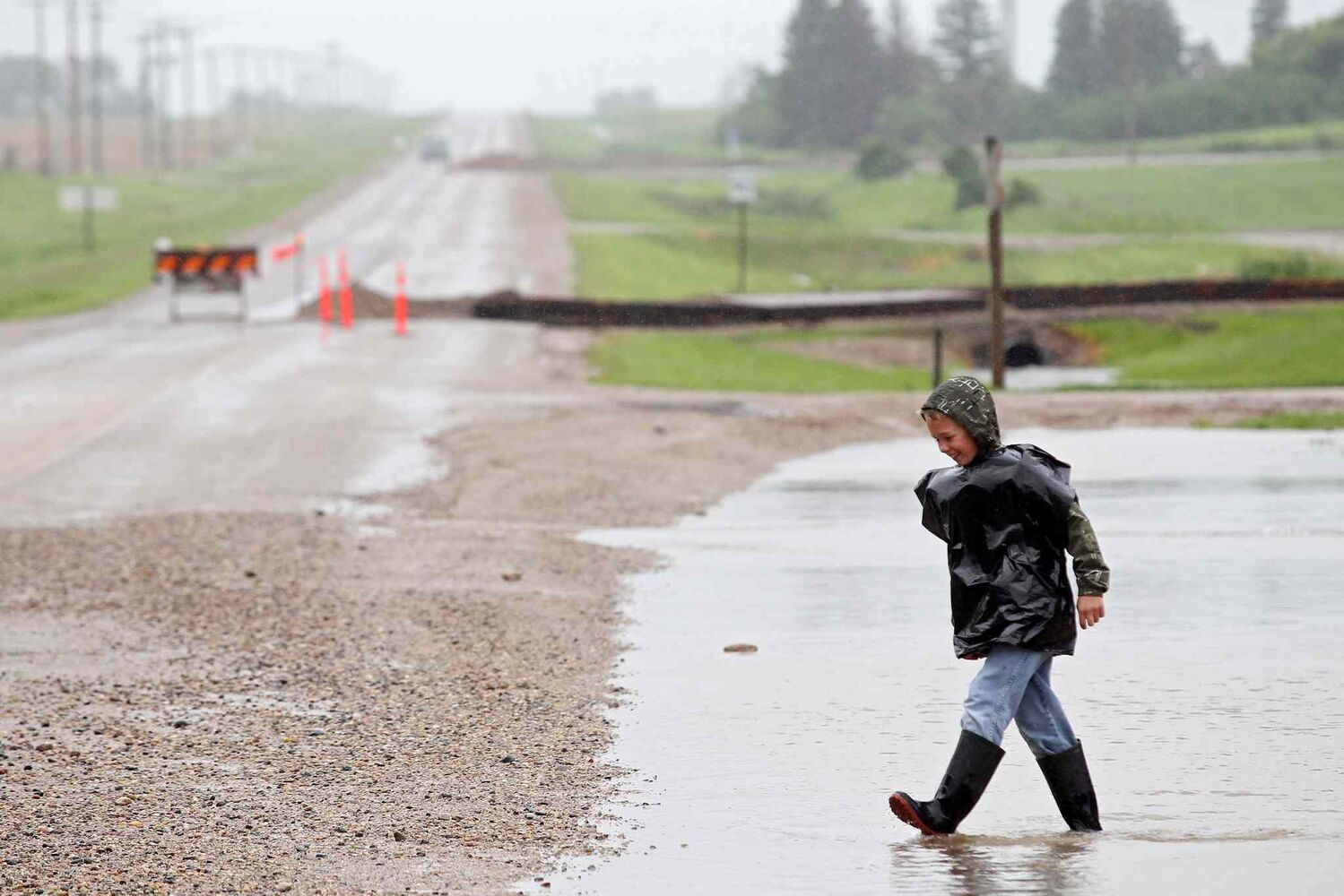A young boy plays in the flood water adjacent to Highway 256 in the village of Cromer. (Tim Smith / Brandon Sun)