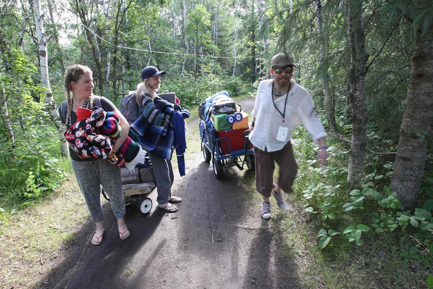 From left: Alysha Guenther, Johanna Johnson and Paul Mann head into the campground to kick off the 2016 Winnipeg Folk Festival at Birds Hill Park Wednesday morning. Performances start tomorrow and will continue until July 10. (JOE BRYKSA / WINNIPEG FREE PRESS)