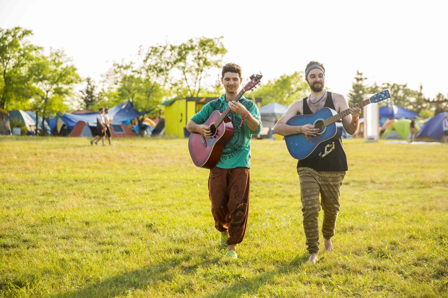 Christian Kuzdub (left) and Alexandre Joyal play guitar while walking through the folk fest campground at Birds Hill Park on Wednesday, July 8, 2015. (Mikaela MacKenzie / Winnipeg Free Press)