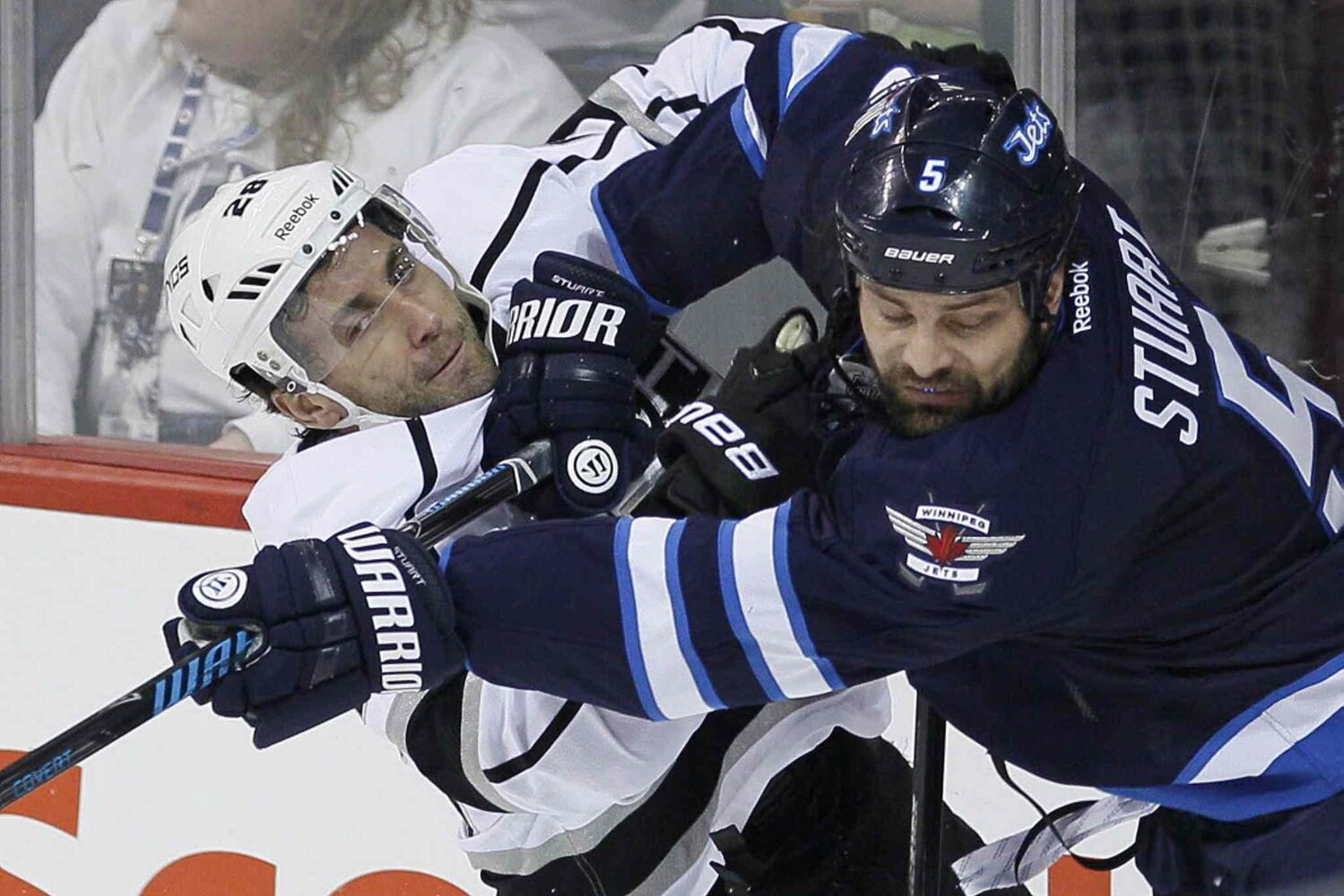 Winnipeg Jets' Mark Stuart (5) checks Los Angeles Kings' Jarret Stoll (28) during the first period in Winnipeg on Thursday. (John Woods / The Canadian Press)