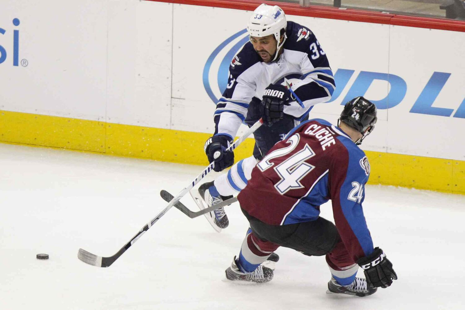 Winnipeg Jets forward Dustin Byfuglien passes the puck behind Marc-Andre Cliche of the Colorado Avalanche. (BARRY GUTIERREZ / THE ASSOCIATED PRESS)