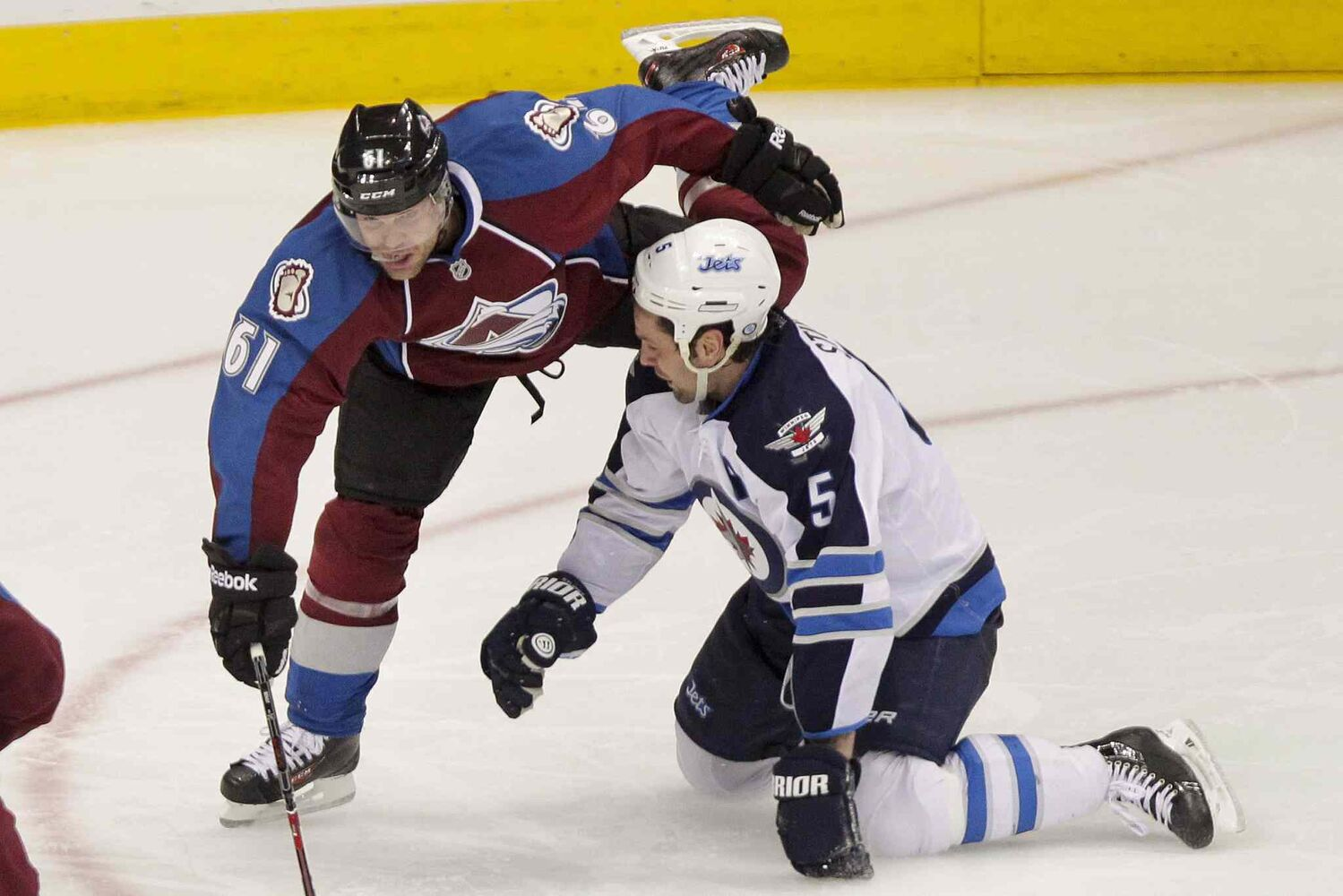 The Colorado Avalanche's Andre Benoit collides with Winnipeg Jets defenceman Mark Stuart during the third period.