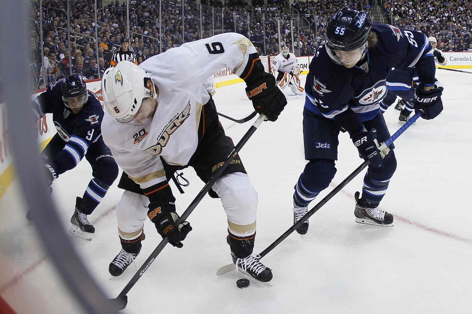Winnipeg Jets' Evander Kane (left) and Mark Scheifele battle in the corner against Anaheim Ducks' Ben Lovejoy during the second period.