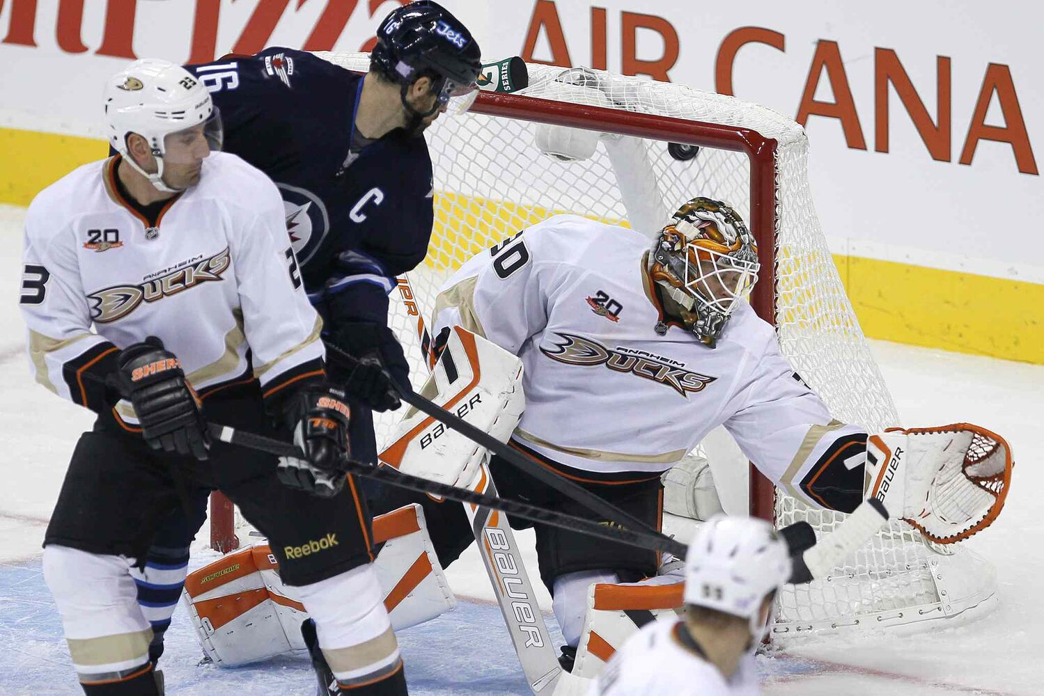 Winnipeg Jets' Andrew Ladd tips Blake Wheeler's shot past Anaheim Ducks goaltender Viktor Fasth as Francois Beauchemin defends in the first period.