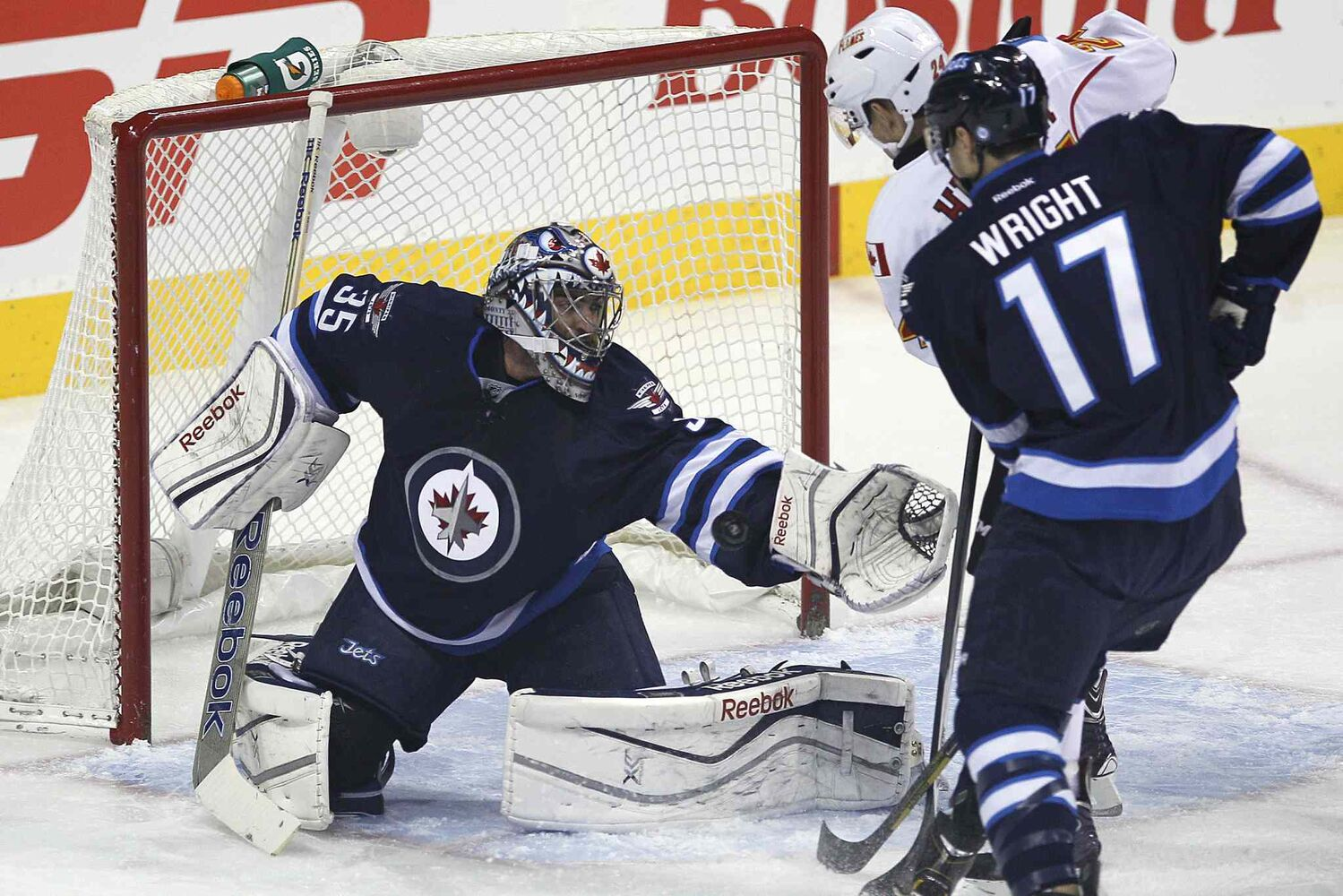 Winnipeg Jets' goaltender Al Montoya (35) stops the shot from the point as Calgary Flames' Jiri Hudler (24) and Jets' Matt Halischuk (15) look for the rebound during first period NHL action in Winnipeg on Monday, Nov. 18, 2013. (John Woods / Winnipeg Free Press)