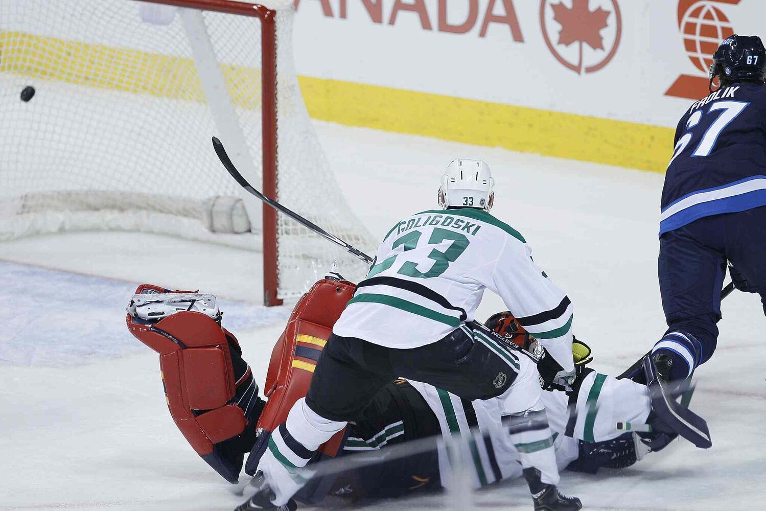 Stars goaltender Tim Thomas can't stop Jets forward Michael Frolik from scoring as the Stars' Alex Goligoski defends during the first period. (JOHN WOODS / WINNIPEG FREE PRESS)