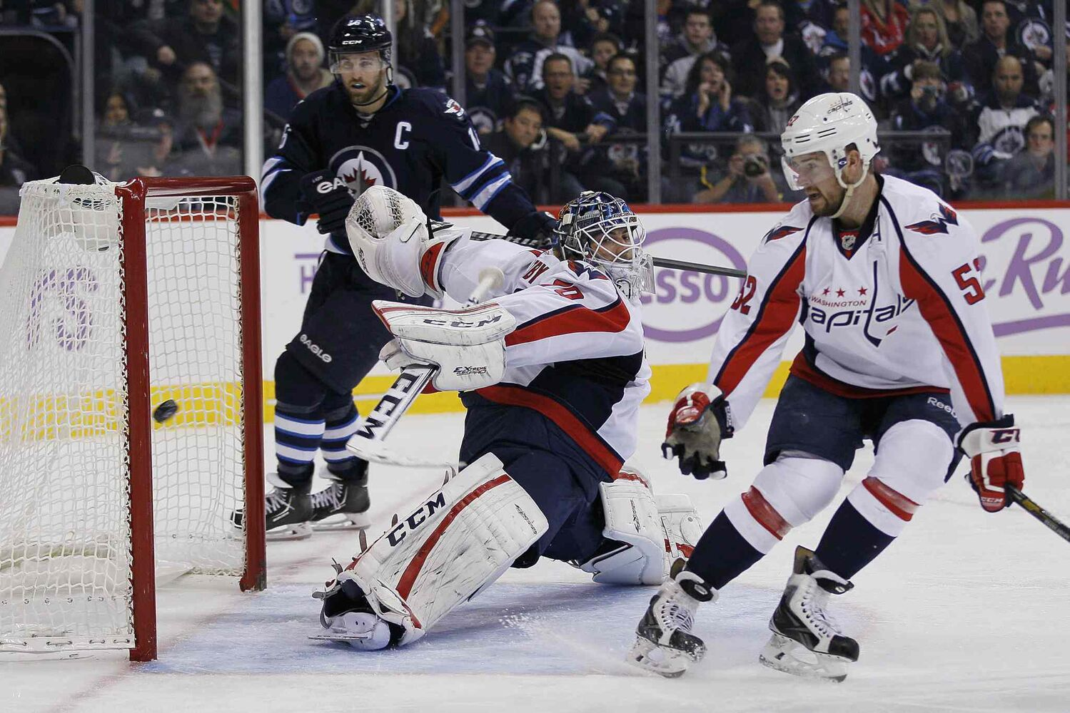 Winnipeg Jets forward Andrew Ladd and Washington Capitals defenceman Mike Green watch as a shot from Jets forward Bryan Little's blasts past Capitals goaltender Braden Holtby during the second period.