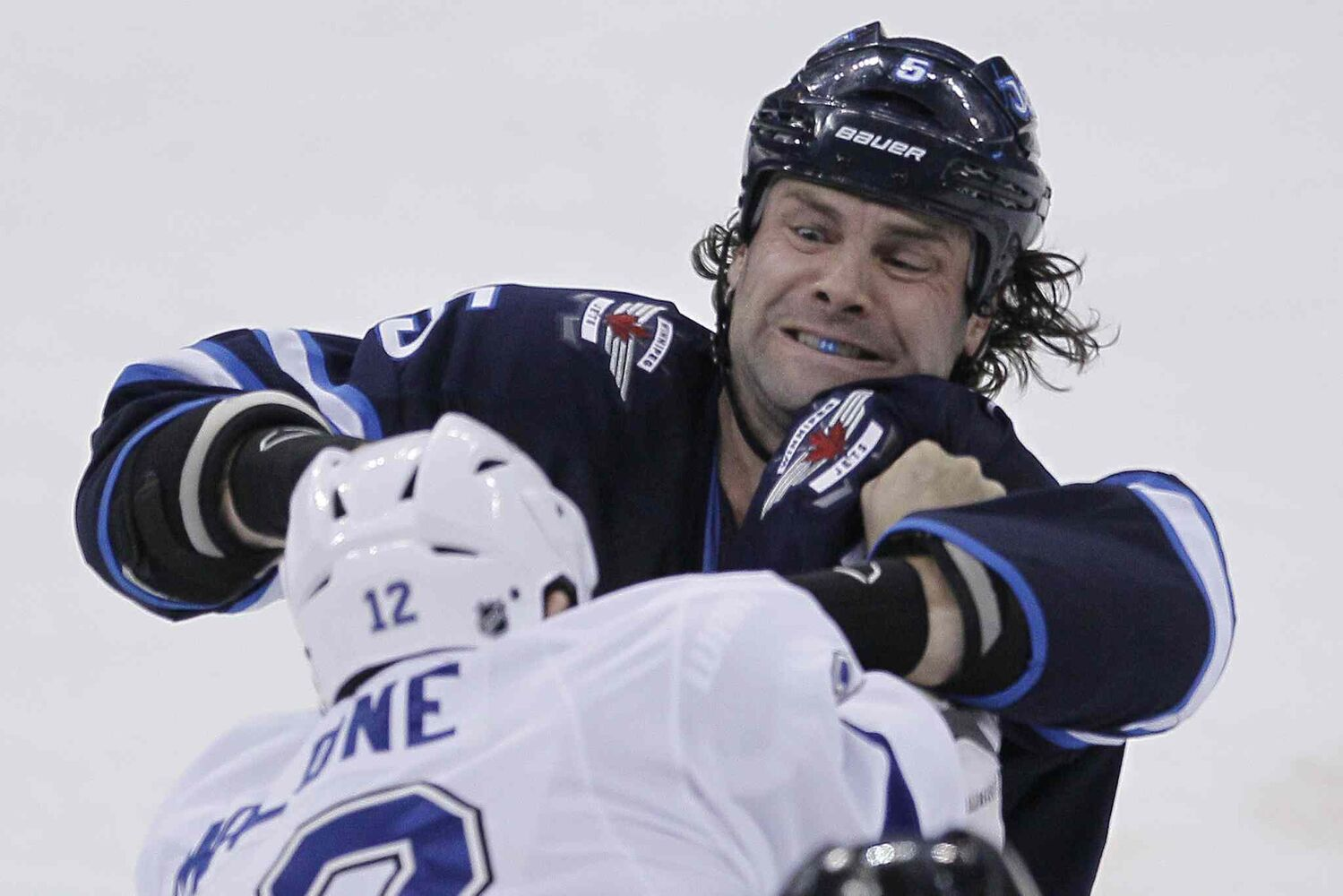 Winnipeg Jets' Mark Stuart (5) and Tampa Bay Lightning's Ryan Malone (12) fight during the first period Tuesday. (John Woods / Winnipeg Free Press)