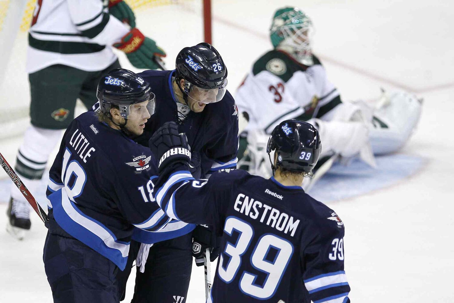 Winnipeg Jets' Bryan Little (left), Blake Wheeler (centre) and Toby Enstrom celebrate Little's goal.