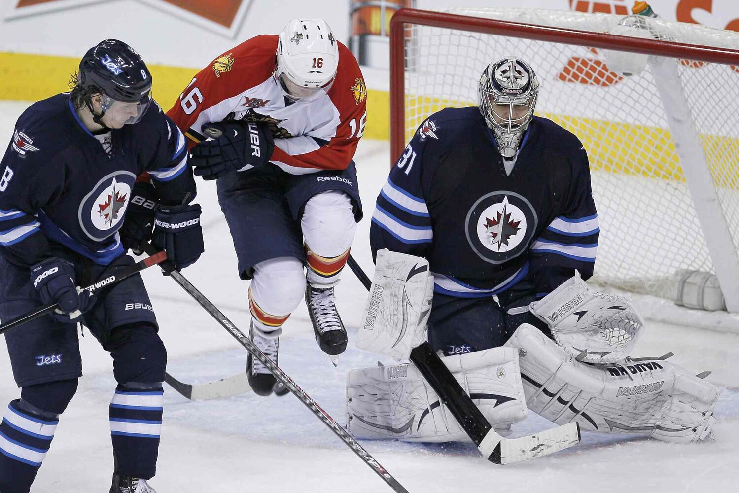 Florida Panthers' Aleksander Barkov (16) jumps to avoid the shot in front of Winnipeg Jets goaltender Ondrej Pavelec (31) as Jacob Trouba (8) looks on during the third period.
