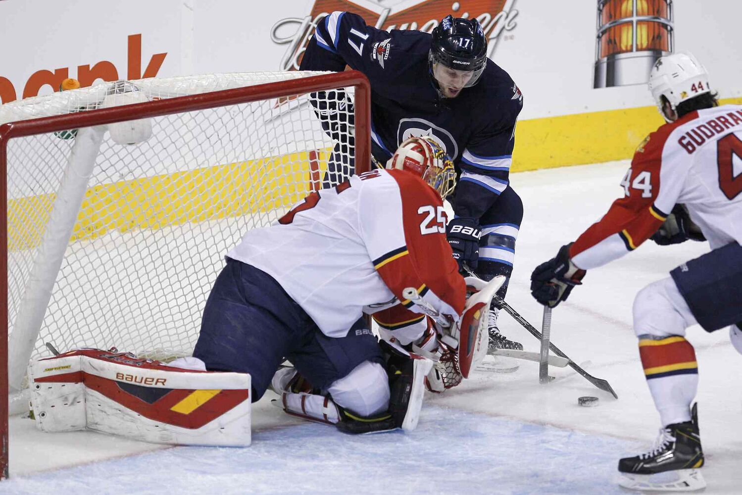 Winnipeg Jets' James Wright (17) tries to jam the puck into the corner of Florida Panthers goaltender Jacob Markstrom's (25) net as Erik Gudbranson (44) looks for the rebound during the  third period.