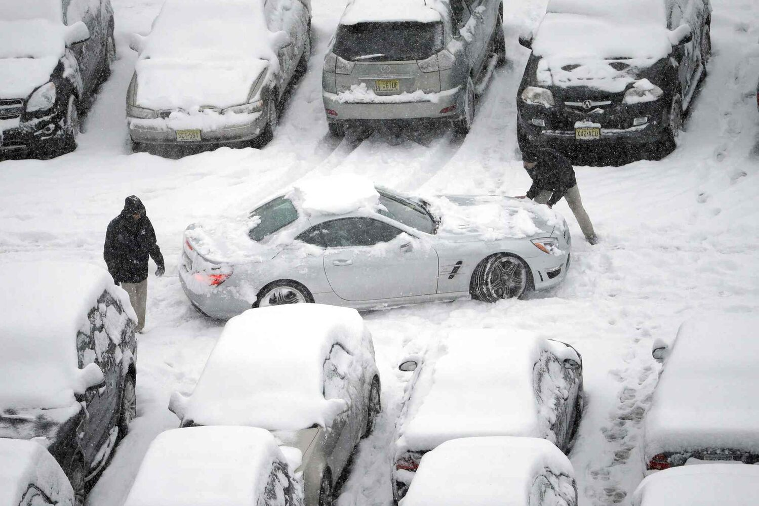 Snow-covered cars occupy a parking lot at Lincoln Financial Field in Philadelphia on Sunday. (Matt Rourke / The Associated Press)