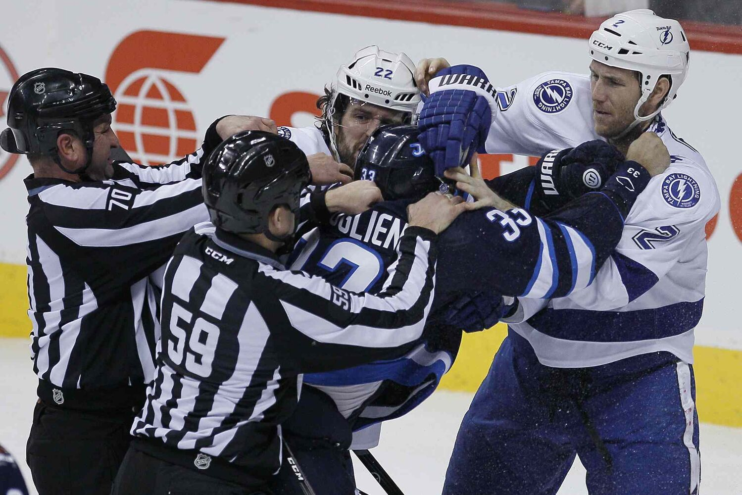 Linesmen hold Winnipeg Jets' Dustin Byfuglien (33) back from Tampa Bay Lightning's Jean-Philippe Cole (22) and Eric Brewer (2) during the third period.